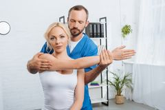 portrait of physiotherapist stretching womans arm