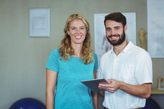 Portrait of physiotherapist and woman standing with digital tablet. Portrait of physiotherapist and women standing with digital tablet in clinic Royalty Free Stock Photo