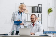 portrait of physiotherapists in white coats and eyeglasses working together