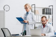 portrait of physiotherapists in white coats and eyeglasses at workplace