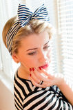 Portrait of pinup girl with red lips and nails looking down dreaming on jalousie sun lighting window Royalty Free Stock Photography