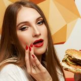 Playful girl posing with burger. Portrait of playful beautiful woman with red lips holding delicious hamburger and looking at it. Flirty female model posing with Stock Image
