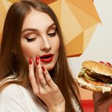 Playful girl posing with burger. Portrait of playful beautiful sexy woman with red lips holding delicious hamburger and looking at it. Flirty female model posing Stock Images