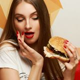 Playful girl posing with burger. Portrait of playful beautiful sexy woman with red lips holding delicious hamburger and looking at it. Flirty female model posing Royalty Free Stock Images