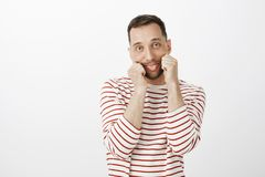 Portrait of playful childish Caucasian guy in striped clothes, pulling mouth with hands and sticking out tongue with. Indifferent bored expression, being tired Royalty Free Stock Photo