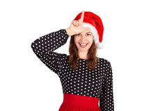 Portrait of playful crazy woman in dress holding hand showing letter L making loser gesture and smiling. emotional girl in santa c royalty free stock image