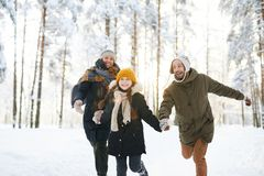 Carefree Family Enjoying Winter. Portrait of playful family running in winter forest all smiling happily in sunlight, copy space stock photo