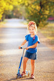Portrait of playful fun smiling little girl with scooter in the Stock Images