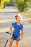 Portrait of playful fun smiling little girl with scooter in the Stock Image