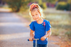 Portrait of playful fun smiling little girl with scooter in the Stock Photos