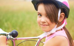 Portrait of a playful funny little girl in a pink safety helmet on her bike. Portrait of a playful funny girl in a pink safety helmet on her bike royalty free stock photography