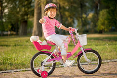 Portrait of a playful funny girl in a pink safety helmet on her Stock Image