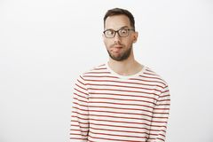 Portrait of playful funny guy with bristle in black eyewear, sticking out tongue and looking at nose, making faces and. Being childish over gray background Royalty Free Stock Images