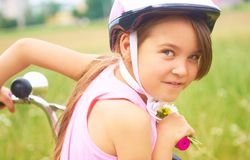 Portrait of a playful funny little girl in a pink safety helmet on her bike. Portrait of a playful funny girl in a pink safety helmet on her bike. Girl in a royalty free stock photo