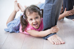 Portrait of playful girl with sister holding father's legs on hardwood floor Royalty Free Stock Photography