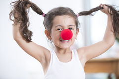 Portrait of playful little girl wearing clown nose holding pigtails at home Stock Photo