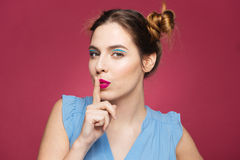 Portrait of playful pretty young woman showing silence sign Stock Image