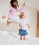 Portrait of playful siblings jumping Stock Images