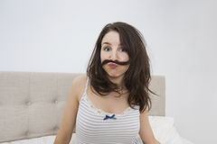 Portrait of playful woman with mustache made of hair in bed Stock Images