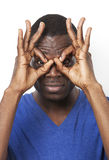 Portrait of playful young man with hands over eyes against white background Royalty Free Stock Image