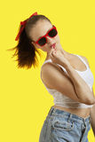Portrait of playful young woman in sunglasses eating lollipop over yellow background Stock Image