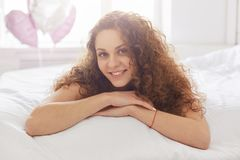Portrait of pleasant looking woman with curly hair, lies on stomach in bed, has positve expression, being pleased or satisfied to stock image
