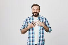 Portrait of pleased adult bearded male with sincere happy smile, holding hands on chest expressing surprise while. Standing over gray background. Employee is Stock Photo