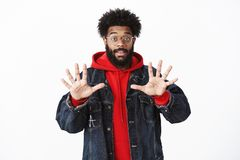 Portrait of pleased and friendly-looking african-american bearded male in glasses raising hands showing number ten or stock photo