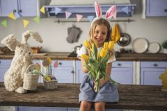 Glad child congratulating on a holiday. Portrait of pleased girl celebrating easter at home. She is extending hand with bunch of yellow tulips Royalty Free Stock Photos