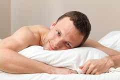Portrait of pleased handsome Caucasian man in bed Royalty Free Stock Photography