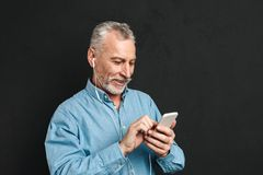 Portrait of pleased male pensioner 60s with gray hair chatting o. R browsing internet on smartphone isolated over black background Stock Image