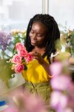 Portrait of pleased woman that counting roses. Really like this. Attentive girl expressing positivity while enjoying her job stock image