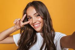 Portrait of pleased woman 20s with long hair laughing while taking selfie photo, isolated over yellow background royalty free stock photos