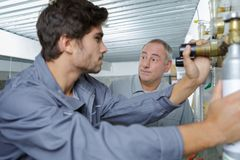 Portrait plumber with apprentice Royalty Free Stock Photography