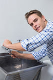 Portrait of plumber fixing water tap with pliers Royalty Free Stock Image