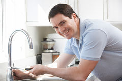 Portrait Of Plumber Mending Kitchen Tap. Portrait Of Smiling Plumber Mending Kitchen Tap Royalty Free Stock Images