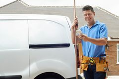 Portrait Of Plumber With Van Texting On Mobile Phone Outside Hou Royalty Free Stock Photo