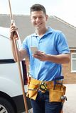 Portrait Of Plumber With Van Texting On Mobile Phone Outside Hou Royalty Free Stock Photos