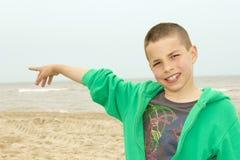 Portrait of a pointing  boy against beach. Portrait of a pointing teenage boy against beach Stock Photo