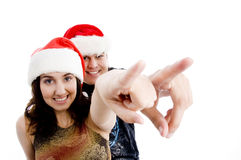 Portrait of pointing couple with christmas hat Royalty Free Stock Images