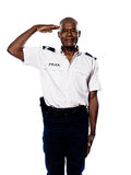 Portrait of police officer saluting. Portrait of an afro American police officer saluting in studio on white isolated background Royalty Free Stock Images
