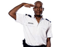 Portrait of a policeman saluting Royalty Free Stock Photography