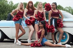 Portrait of pompom girls posing near vintage chevrolet car  at Fun car show event stock images
