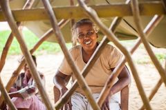 Portrait of a poor, elderly Indian woman behind a fence in the form of a lattice royalty free stock image