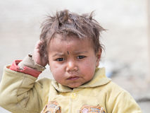 Portrait poor young boy in India. LEH, INDIA - JUNE 29, 2015: Unidentified poor Indian beggar boy on street in Ladakh. Children of the early ages are often Royalty Free Stock Image