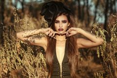 Portrait of a posh dangerous tattooed witch wearing sexy corset dress and vintage silk hat standing in the woods Royalty Free Stock Photos