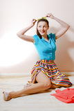Portrait of posing sexy brunette young lady in a striped skirt and blue shirt holding green ribbon. Picture of beautiful sexy pinup girl in a striped skirt and Royalty Free Stock Photos