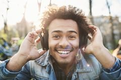 Portrait of positive adult dark-skinned man smiling broadly while sitting in park, listening to music in headphones and