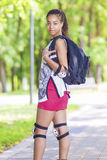 Portrait of Positive African American Teenage Girl. Posing with Backpack and Knee Protectors Outdoors in Park Stock Images