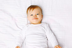 Portrait positive baby lying on the bed Royalty Free Stock Images